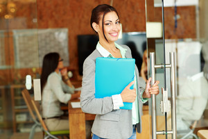 Cheerful cute businesswoman standing with folder in office