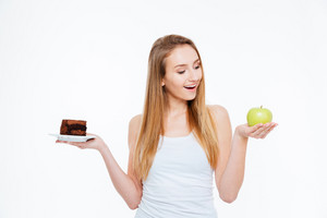 Cheerful excited young woman choosing between healthy and unhealthy food over white background