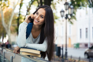 Cheerful female student talking on the phone