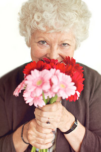Cheerful grandmother happy to have received flowers on mother's day