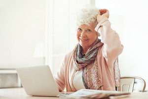 Cheerful grandmother sitting at home using her laptop