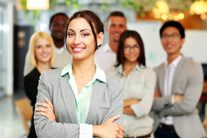 Cheerful group of co-workers standing in office