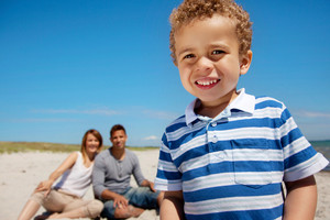Cheerful kid having fun outdoors with his mom and dad in the background