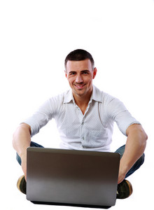 Cheerful man sitting at the floor with laptop over white background