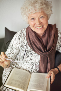 Cheerful mature lady at home enjoying a good book