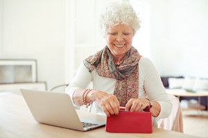 Cheerful old woman in front of laptop getting something from her wallet