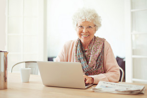 Cheerful senior woman using laptop as recreation at home