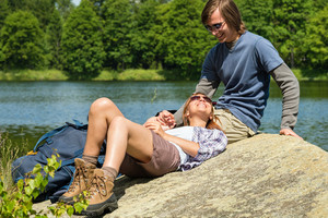Cheerful trekking couple resting at lakeside
