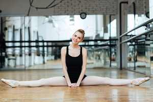 Cheerful woman doing splits in ballet class and looking at camera