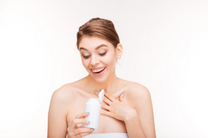 Cheerful woman holding bottle with pills isolated on a white background