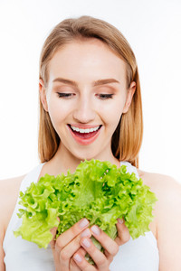 Cheerful woman holding green salad isolated on a white background
