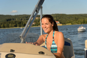Cheerful woman in bikini navigating powerboat in summer