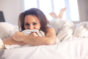Cheerful woman indoor lying on her bed having fun