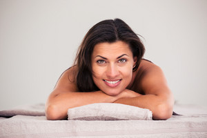 Cheerful woman lying on massage lounger in a wellness center and looking at camera
