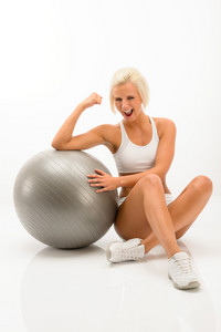 Cheerful woman posing with fitness ball isolated white background