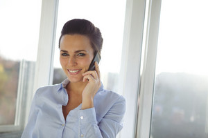 Cheerful young business woman standing in office talking on her mobile phone looking at camera. Beautiful caucasian female model using cell phone.