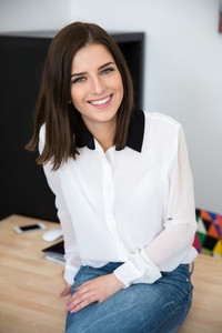 Cheerful young businesswoman sitting on the table in office