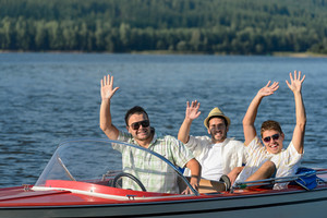 Cheerful young guys in sunglasses partying in speed boat
