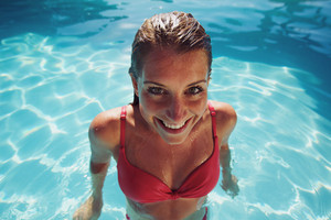 Cheerful young lady in a swimming pool looking at camera. Female in bikini smiling at camera.