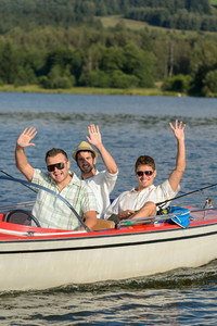 Cheerful young men sitting in motorboat enjoying sunshine