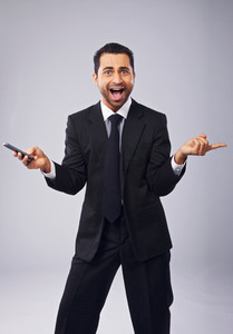 Cheerful young professional holding a phone while gesturing