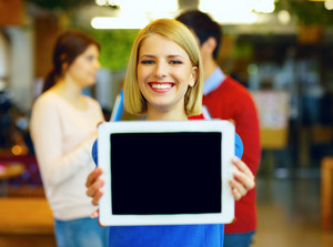 Cheerful young student showing tablet screen