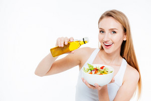 Cheerful young woman poured oil into salad isolated on a white background