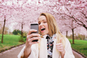 Cheerful young woman talking her picture with her cell phone and gesturing thumbs up sign. Caucasian female model photographing herself with smart phone at spring park.