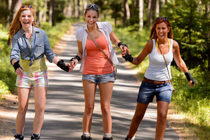Cheerful young women on roller skates holding hands outdoor summertime