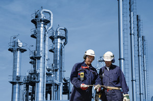 chemical engineers with refinery in background