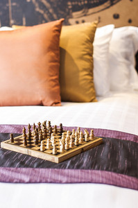 Chess on bed in hotel room