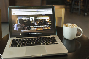 CHIANG MAI, THAILAND - OCTOBER 02, 2014: Starbucks coffee caramel latte and Apple laptop open Starbucks website on monitor.
