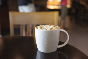 CHIANG MAI, THAILAND - OCTOBER 02, 2014: Starbucks coffee caramel latte white mug in Starbucks Cafe Chiang Mai Thailand. Starbucks is the largest coffeehouse company in the world.