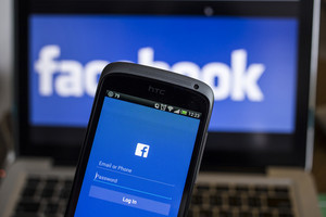 CHIANG MAI, THAILAND - OCTOBER 21, 2014: Facebook application sign in page on smartphone and facebook logo on background. Facebook is largest and most popular social networking site in the world.