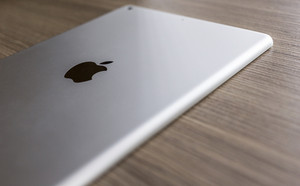 CHIANG MAI, THAILAND - OCTOBER 21, 2014: Logo of Apple in back Apple iPad air on wood desk.