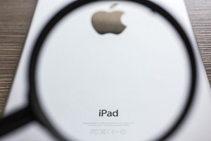 CHIANG MAI, THAILAND - OCTOBER 21, 2014: Magnification glass focus on Logo of Apple in back Apple iPad air on wood desk.