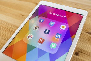 Popular Apple social media apps icons shown on an Apple iPad Air device screen on a wood background.