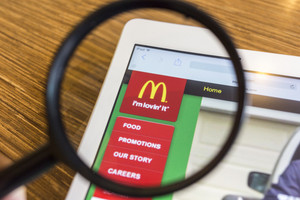 CHIANG MAI, THAILAND - SEPTEMBER 17, 2014: Close up of McDonald's homepage on Apple iPad Air through a magnifying glass on wood table.