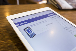 CHIANG MAI, THAILAND - SEPTEMBER 17, 2014: Magnifying glass of Facebook page view on web browser Apple iPad Air device.