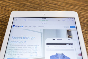 CHIANG MAI, THAILAND - SEPTEMBER 17, 2014: Paypal website displayed on Apple iPad Air tablet screen wood background. Established in 1999, PayPal allows payments and money transfers to be made through the Internet.