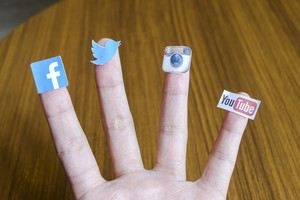 CHIANG MAI, THAILAND - SEPTEMBER 24, 2014: Social media brands printed on sticker and placed on human finger. Include Facebook, Twitter, Instagram and Youtube.