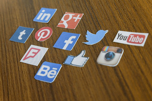 CHIANG MAI, THAILAND - SEPTEMBER 24, 2014: Social media brands printed on sticker and placed on wood table.