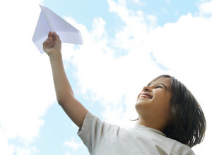 Child holding a paper airplane and dreaming about traveling
