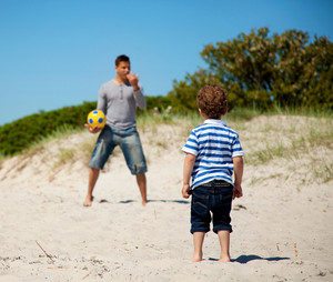 Child looking at his dad teaching him how to play soccer outdoors