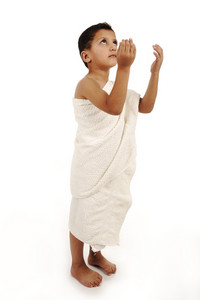 Child muslim pilgrim in white traditional clothes isolated