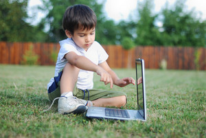 child on the grass with laptop