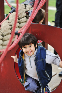 Child playing in park with ropes and climbing