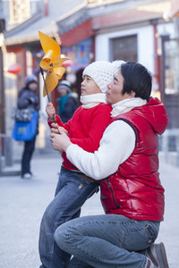 Child playing with pinwheel dressed in holiday attire