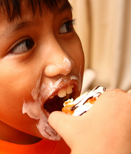 Child With A Messy Face Eating A Cream Cake