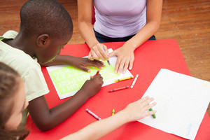 children drawing with her teacher